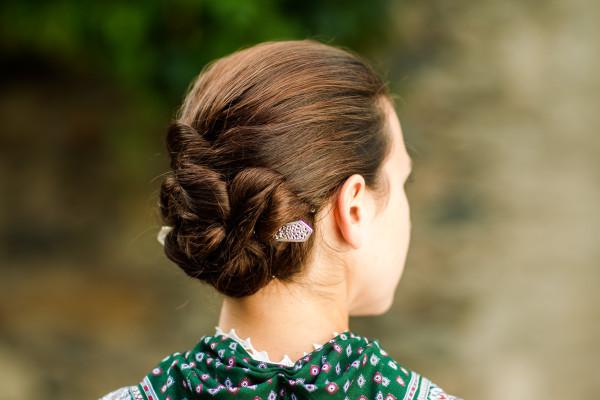 """Beim """"Bäurischen Gewand"""" werden die Haare im Nacken aufgesteckt oder zu einem Knoten verschlungen. Dieser wird von der zierlich gearbeiteten Haarnadel durchbrochen."""